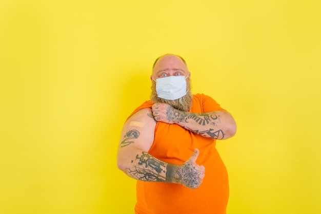 Homem com barba e tatuagens aplicou a vacina contra o vírus covid-19