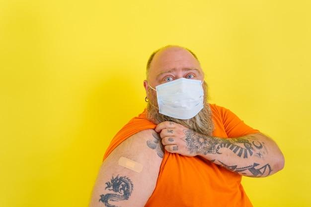 Homem com barba e tatuagens fez a vacina contra cobiça
