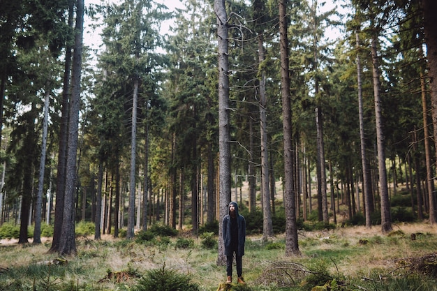 Homem com barba em uma floresta verde com muitas árvores