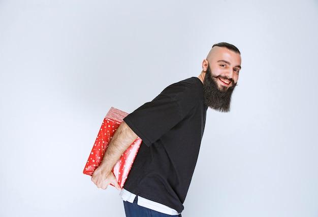 Homem com barba escondendo uma caixa de presente vermelha atrás de si.