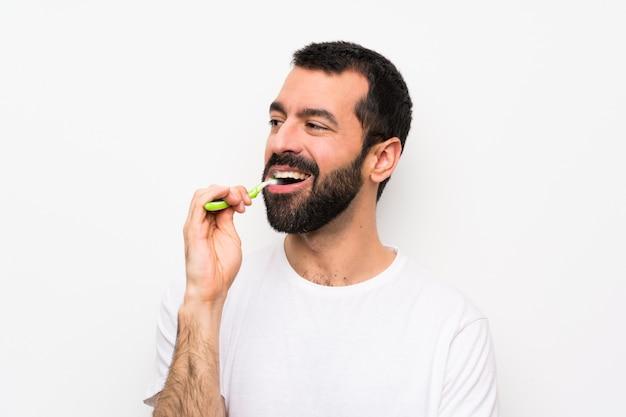Homem com barba, escovar os dentes sobre parede branca isolada