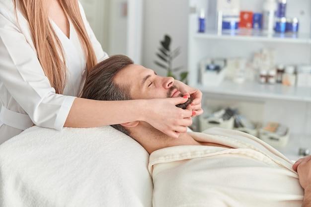 Homem com barba está deitado de costas, recebendo massagem de lifting facial. tratamento de beleza com massagem facial. conceito de bem-estar, beleza e relaxamento.