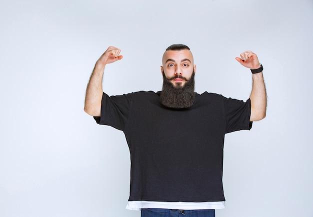 Homem com barba fica extremamente feliz por causa de alguma coisa.