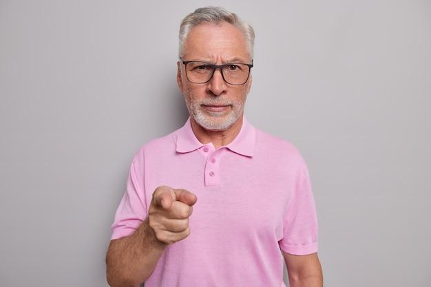 Homem com barba grisalha aponta o dedo indicador para frente e pede para ajudá-lo a usar óculos para uma boa visão camiseta casual rosa isolada em estúdio cinza