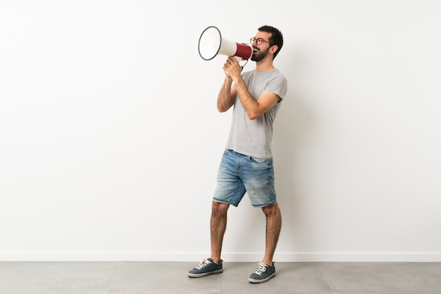 Homem com barba gritando através de um megafone