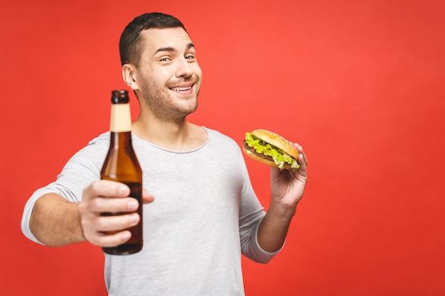Homem com barba isolada sobre fundo vermelho segura um hambúrguer e uma garrafa de cerveja, retrato