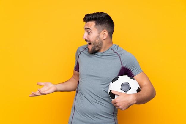 Homem com barba jogando futebol sobre parede isolada