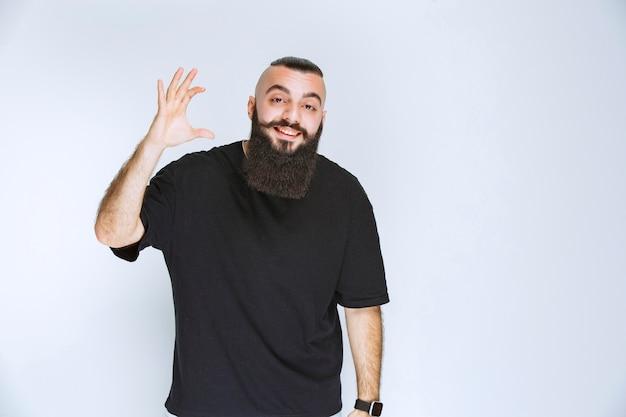 Homem com barba, mostrando as dimensões de um objeto.
