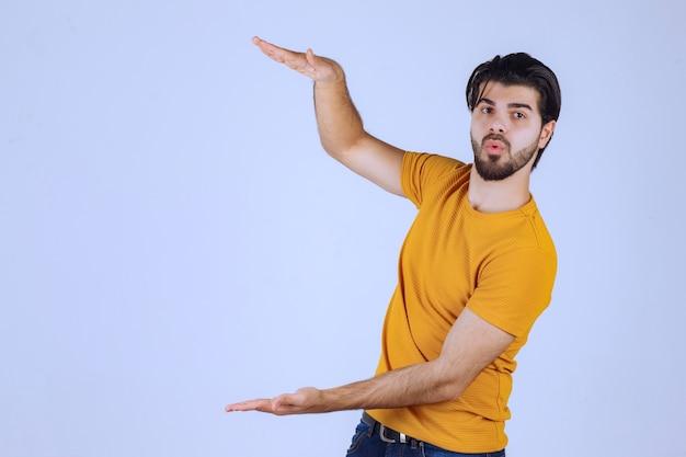 Homem com barba, mostrando as medidas estimadas de um objeto.