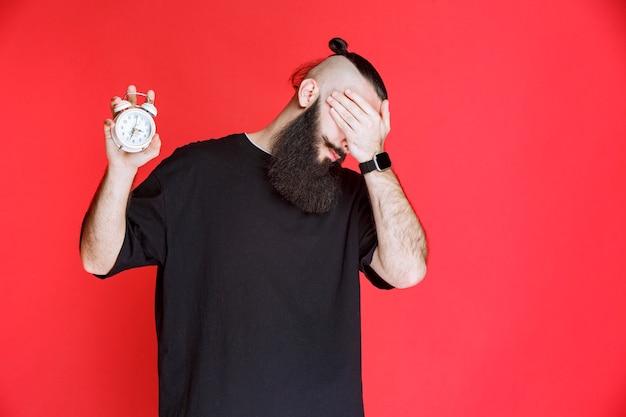 Homem com barba, mostrando o despertador e dormindo.