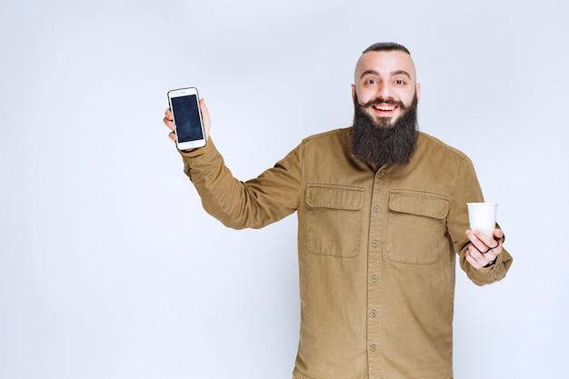Homem com barba, mostrando seu smartphone, segurando uma xícara de café.