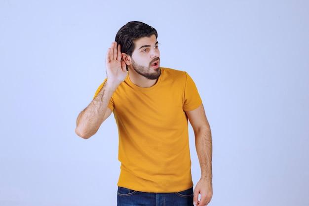 Homem com barba mostrando sua audição e tentando ouvir com atenção