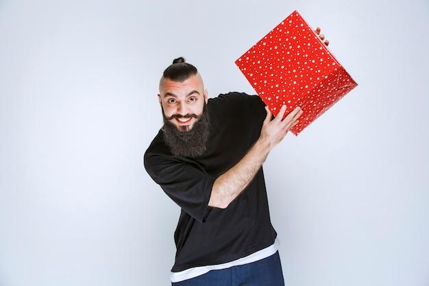 Homem com barba, mostrando sua caixa de presente vermelha.