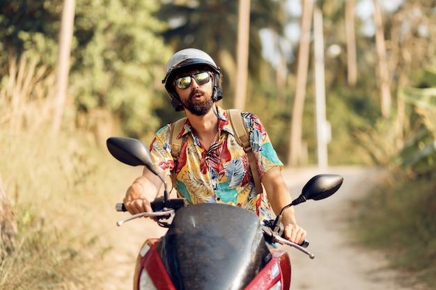Homem com barba na camisa tropical colorida, sentado na moto