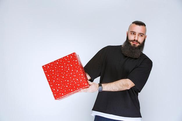 Homem com barba oferecendo caixa de presente vermelha
