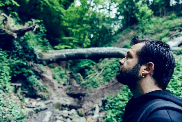 Homem com barba, olhando para a floresta