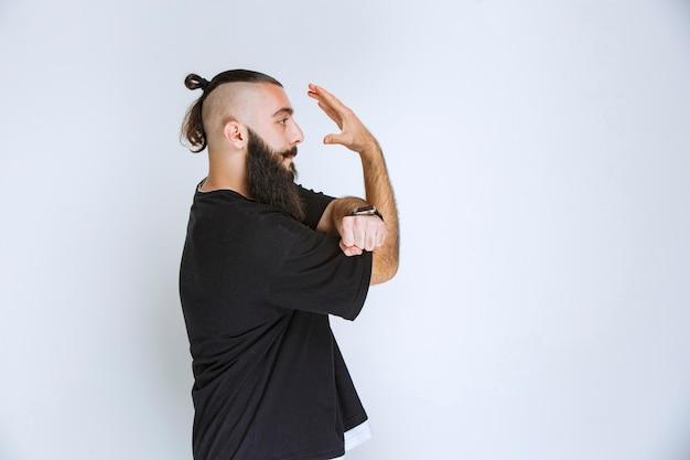 Homem com barba, parando algo com a mão aberta.