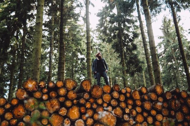 Homem com barba passa por madeira na floresta