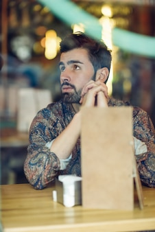 Homem com barba pensativo com roupas casuais sentado em um pub moderno.