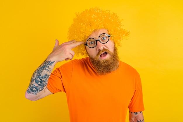 Homem com barba, peruca amarela e óculos fazendo um gesto de arma com a mão