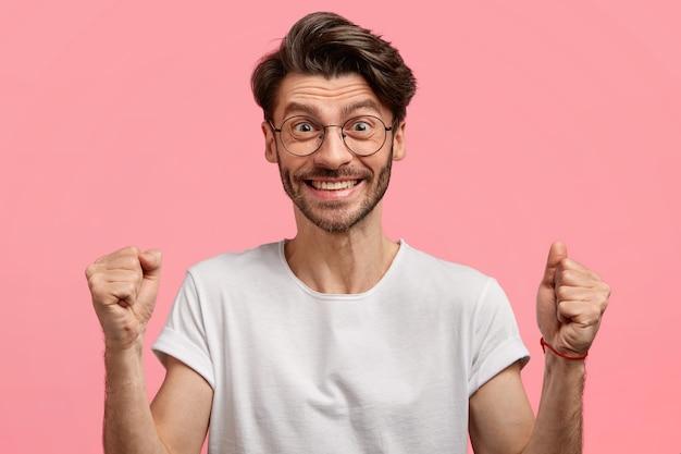 Homem com barba por fazer, emotivo e satisfeito com corte de cabelo da moda, barba por fazer, cerrou os punhos com sucesso e vitória, usa camiseta branca e óculos, isolado sobre o espaço rosa