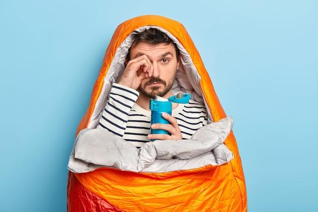 Homem com barba por fazer esfrega os olhos, tem uma expressão sonolenta, acampa, relaxa no saco de dormir, aproveita o fim de semana de aventura