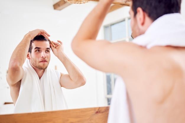 Homem com barba por fazer penteando o cabelo em pé com uma toalha branca no pescoço perto do espelho do banheiro