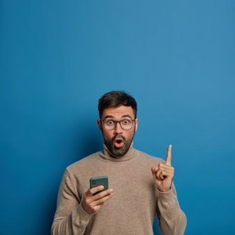 Homem com barba por fazer surpreso segura o telefone, mostra o espaço vazio acima, aponta o dedo indicador, usa óculos e macacão marrom, mantém a boca aberta, isolada sobre fundo azul.