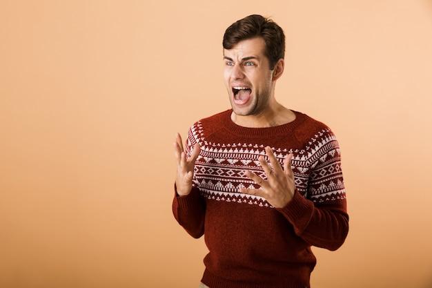 Homem com barba por fazer, vestindo um suéter de tricô, gritando e expressando indignação, isolado sobre uma parede bege