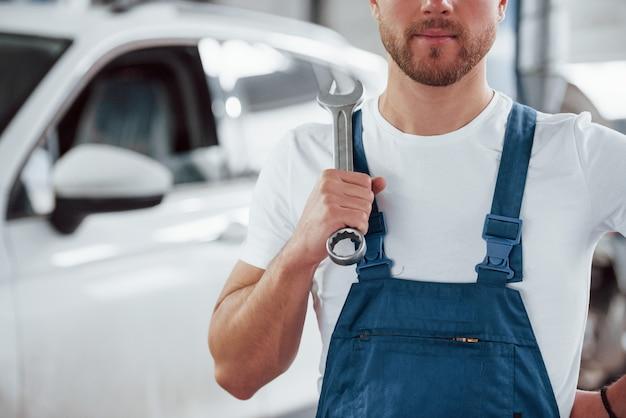 Homem com barba rala. funcionário com uniforme azul trabalha no salão automóvel