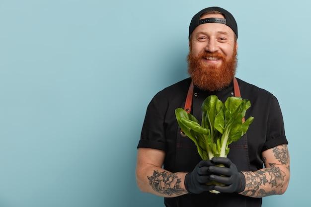 Homem com barba ruiva, avental e luvas segurando uma salada