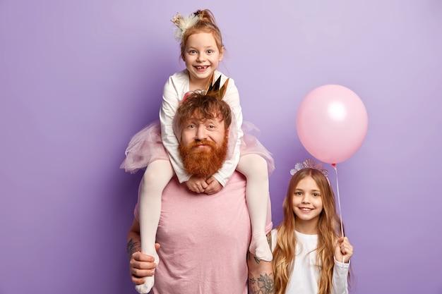 Homem com barba ruiva e suas filhas com acessórios de festa