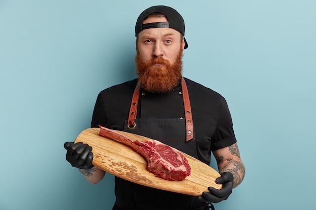 Homem com barba ruiva em avental e luvas segurando uma placa de madeira com um pedaço de carne