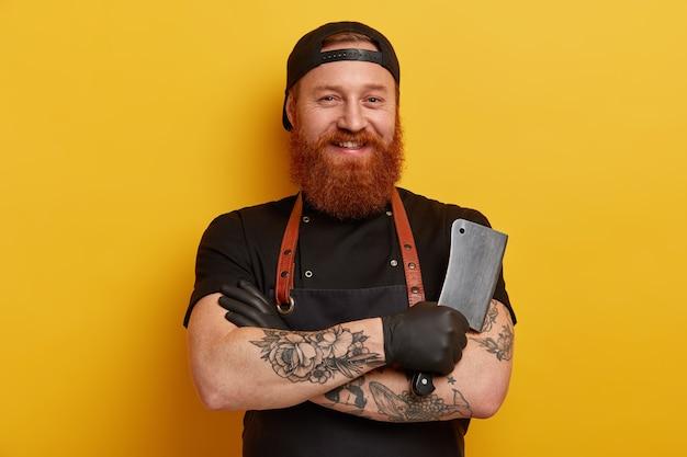 Homem com barba ruiva em avental e luvas