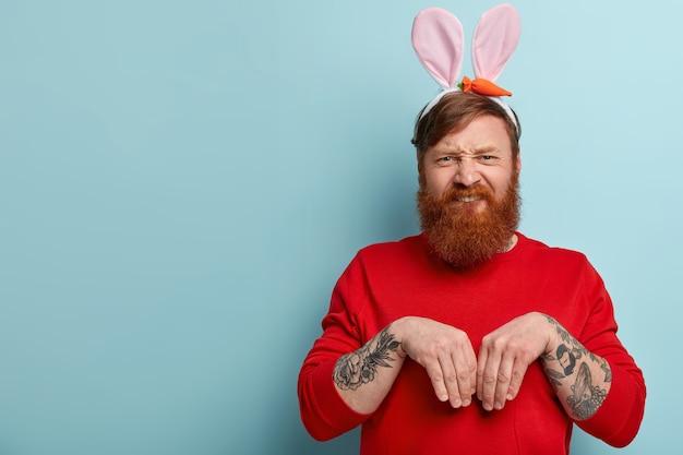 Homem com barba ruiva, roupas coloridas e orelhas de coelho