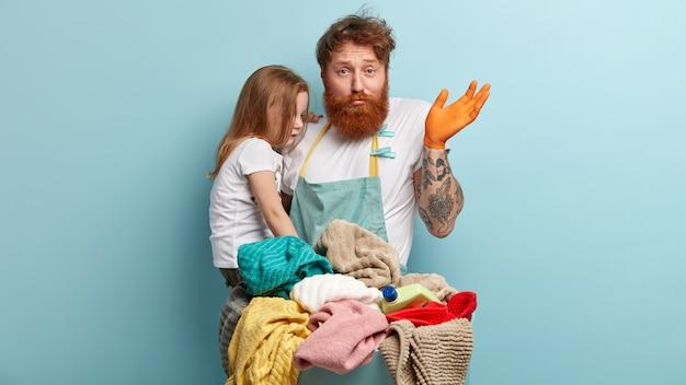 Homem com barba ruiva segurando a filha e lavando roupa