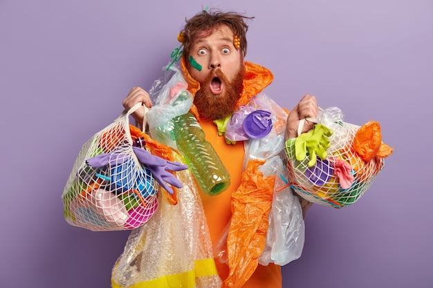 Homem com barba ruiva segurando sacolas com lixo plástico