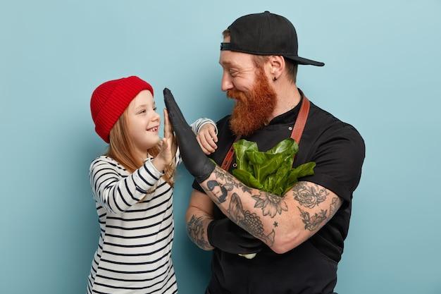 Homem com barba ruiva usando avental e luvas de colo na filha