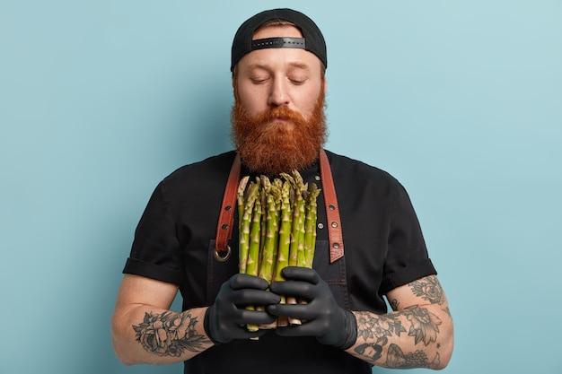 Homem com barba ruiva usando avental e luvas segurando aspargos