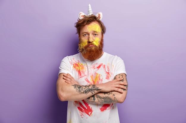 Homem com barba ruiva usando bandana de unicórnio e camiseta suja