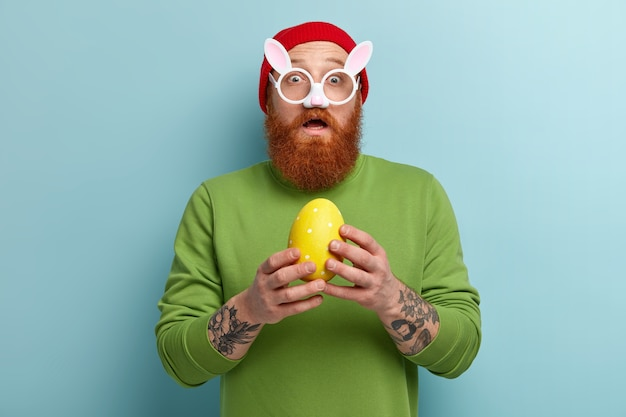 Homem com barba ruiva usando roupas coloridas e óculos com orelhas de coelho