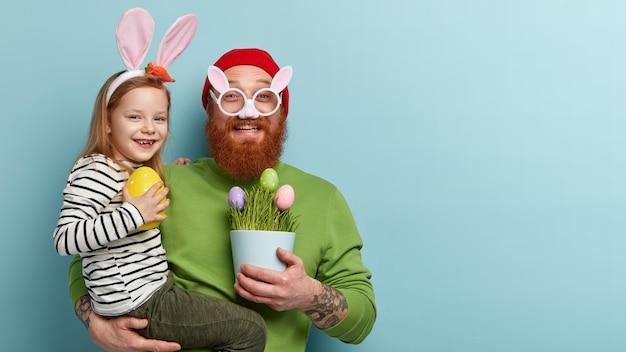 Homem com barba ruiva vestindo roupas coloridas e segurando a filha