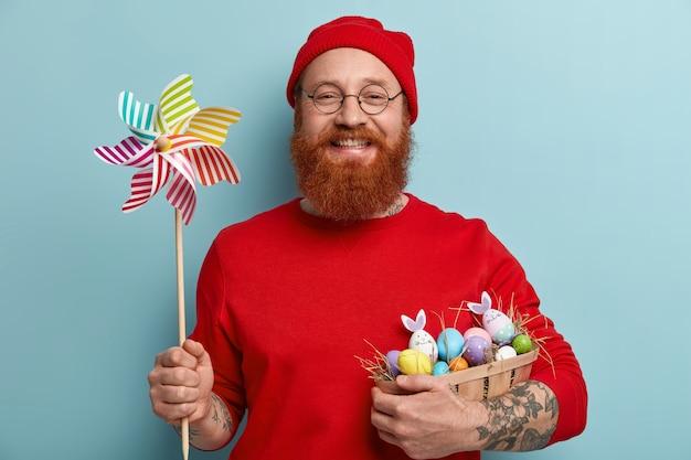Homem com barba ruiva, vestindo roupas coloridas e segurando ovos de páscoa