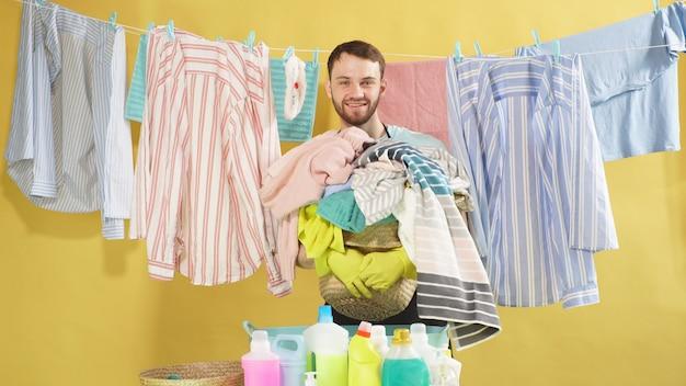Homem com barba segura um cesto de roupa suja e contra uma parede isolada. roupas limpas penduram em um varal