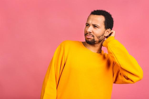 Homem com barba, segurando a mão perto da orelha, tentando ouvir notícias interessantes, expressando o conceito de comunicação e fofocas isoladas sobre rosa.