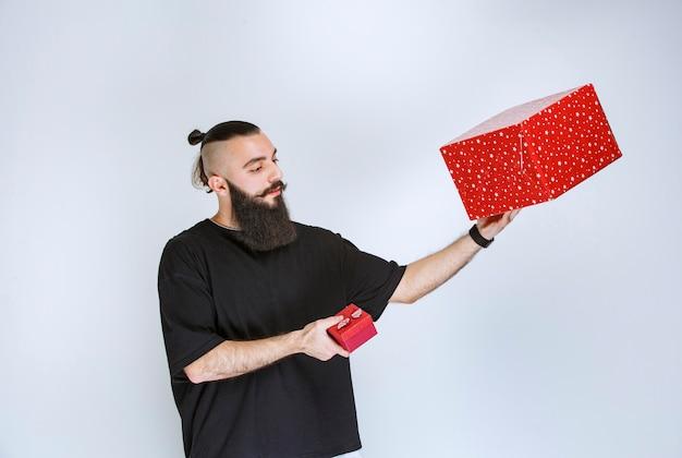 Homem com barba segurando caixas de presente vermelhas com as duas mãos e tomando uma decisão.