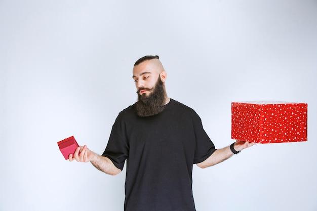 Homem com barba segurando caixas de presente vermelhas e hesitando em fazer a escolha.