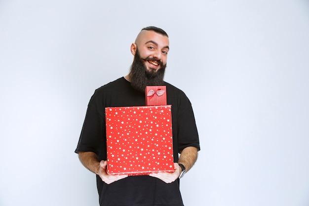 Homem com barba segurando caixas de presente vermelhas e oferecendo-as à namorada.