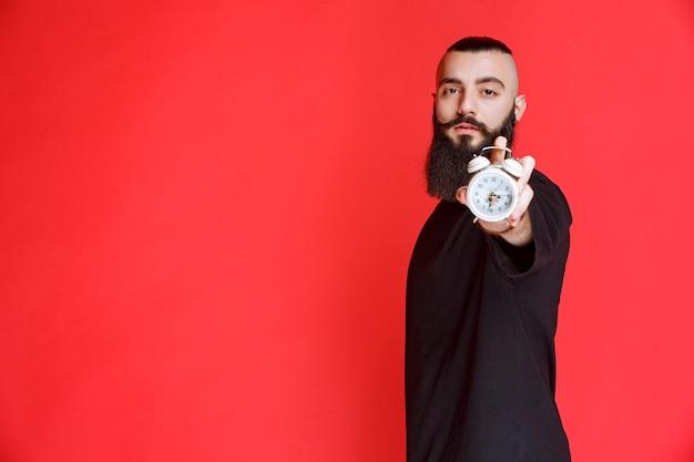 Homem com barba segurando e promovendo um despertador como um produto.