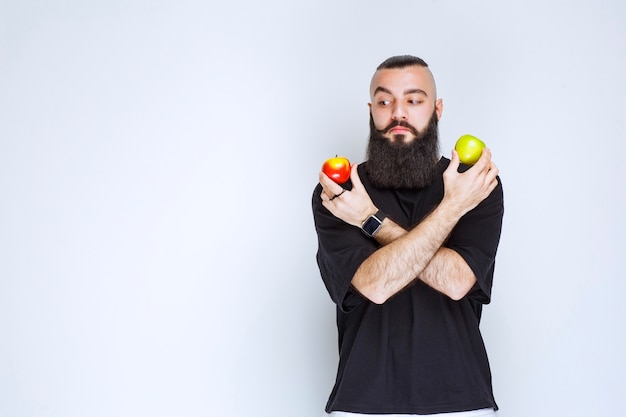 Homem com barba segurando maçãs vermelhas e verdes na mão.